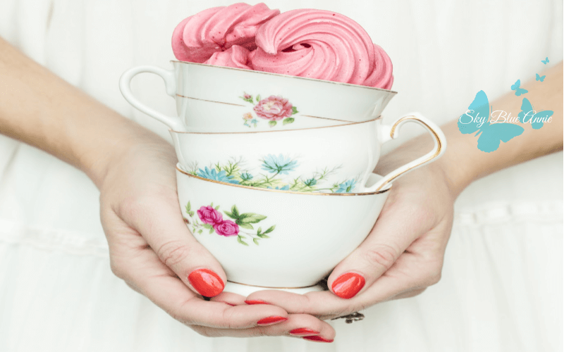 Woman Holding a Stack of Pretty Tea Cups